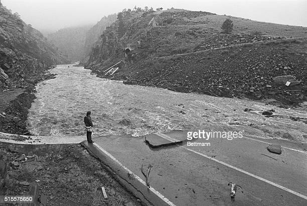 A rescue worker scans the flood swollen Big Thompson River for possible flood victims where Highway ends in the Big Thompson Canyon here 8/2 A flash...