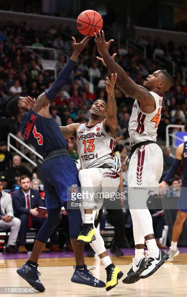 Lovell Cabbil Jr #3 of the Liberty Flames competes for a rebound with Ahmed Hill and Ty Outlaw of the Virginia Tech Hokies in the second half during...