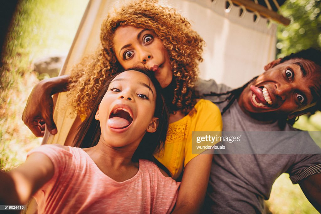 Lovely African-American family making silly faces and posing : Stock Photo