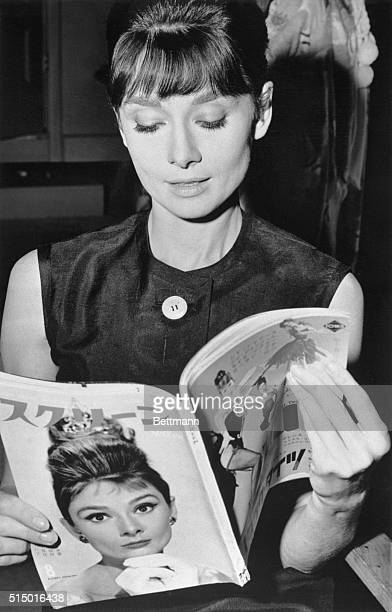 Lovely Audrey Hepburn looks at a cover story about herself in a Japanese magazine, while relaxing on the set of The Children's Hour while it was...