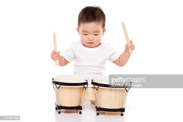 Lovely baby boy playing bongo drum
