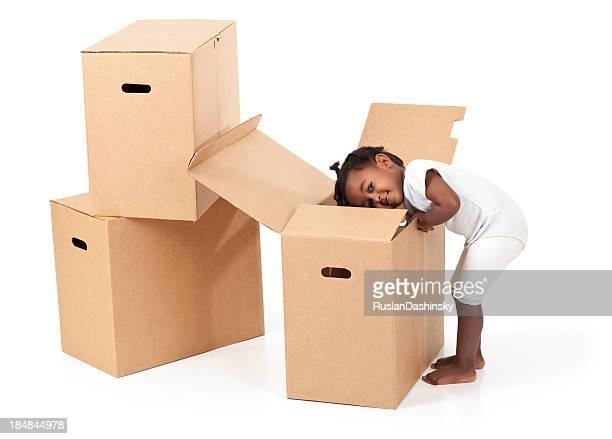 Schöne baby Mädchen rummaging in einen Pappkarton ablegen.