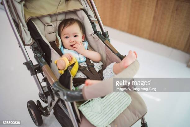 Lovely baby sitting in the baby stroller smiling at camera joyfully