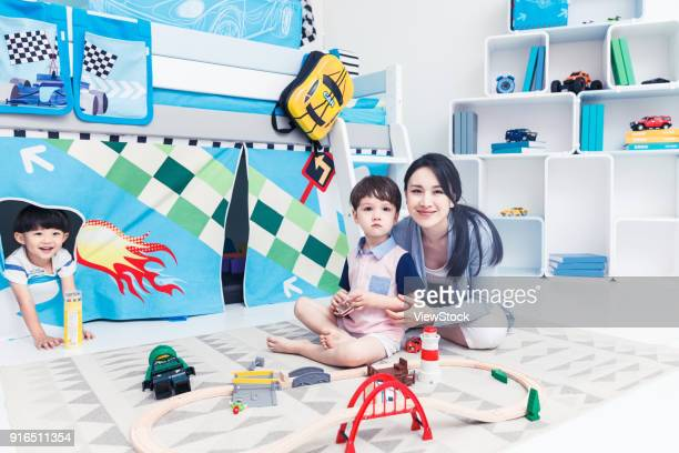 Lovely boy and teachers play in the game room
