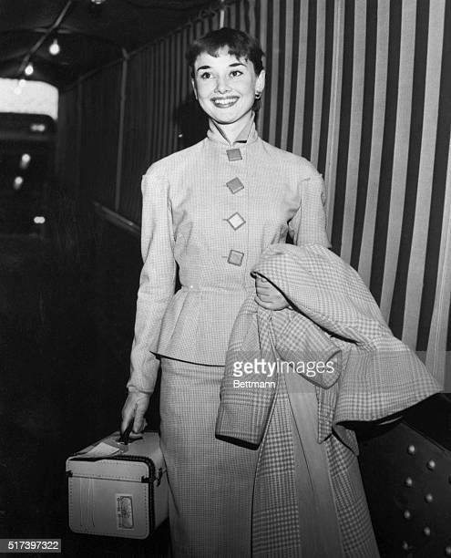 Lovely British actress Audrey Hepburn lights up with a charming smile as she leaves the Queen Mary October 4 upon her arrival from England Miss...
