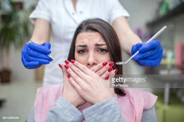 lovely brunette fearing the examination at the dentist - dental fear stock pictures, royalty-free photos & images