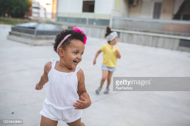 lovely cheerful children running outdoors - kids playing tag stock photos and pictures