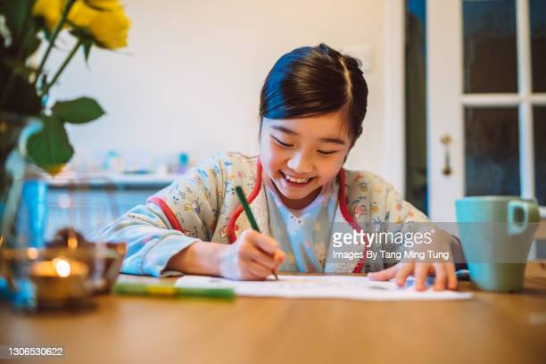 lovely cheerful girl doing homework on dining table at home - human age stock pictures, royalty-free photos & images