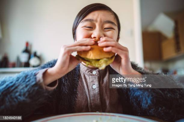 lovely cheerful girl enjoying her homemade burger at home - table stock pictures, royalty-free photos & images