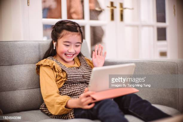 lovely cheerful girl having video call with family on digital tablet at home - digital native stock pictures, royalty-free photos & images