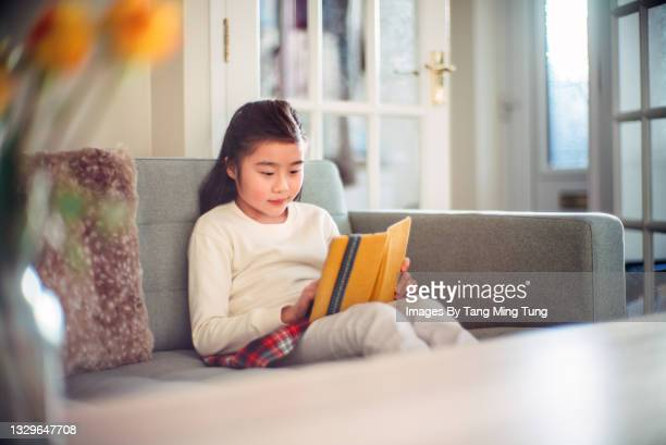lovely cheerful girl reading an electronic book with her ebook reader while sitting relaxingly on sofa at home - digital native stock pictures, royalty-free photos & images