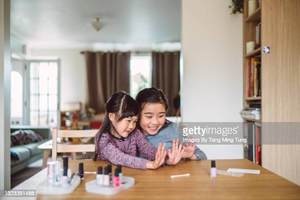 lovely cheerful little girl showing her polished fingernails to her sister while they are varnishing their fingernails at home - human finger stock pictures, royalty-free photos & images