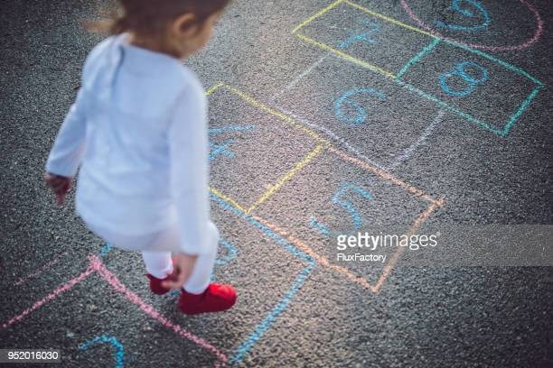 lovely child playing in the park - hopscotch stock pictures, royalty-free photos & images
