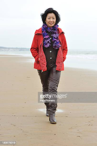 Lovely Chinese mature woman walking on the beach