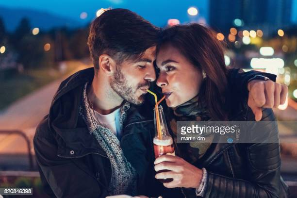 Lovely couple at the rooftop drinking cider from one bottle with drinking straw