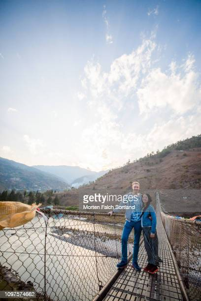 lovely couple by the bridge in punakha, bhutan - suspension bridge stock pictures, royalty-free photos & images
