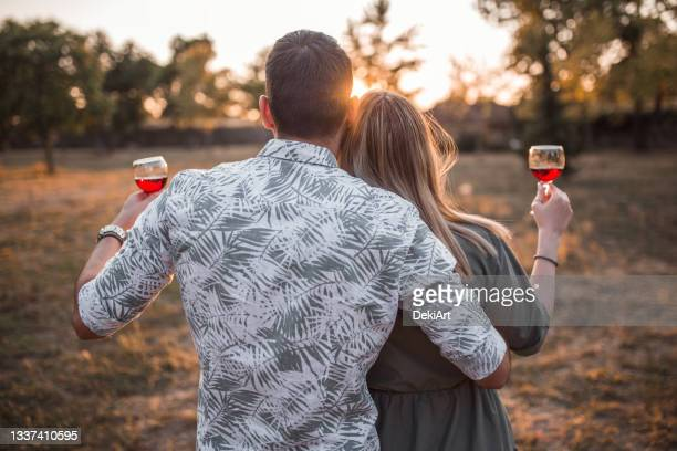 lovely couple celebrating their engagement and looking at sunset - fiancé stock pictures, royalty-free photos & images
