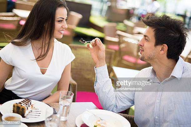Lovely couple eating dessert in cafe