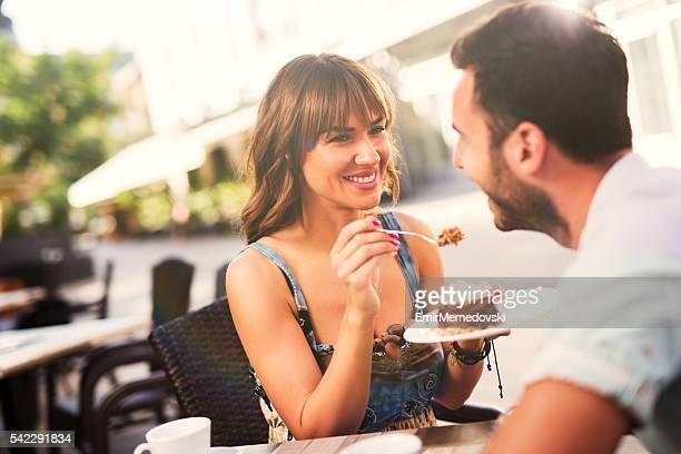 Encantadora pareja disfrutando de un postre en la cafetería.