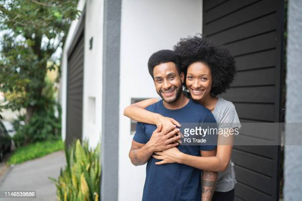 mooie paar glimlachen buitenshuis in de voorkant van het huis - voor stockfoto's en -beelden