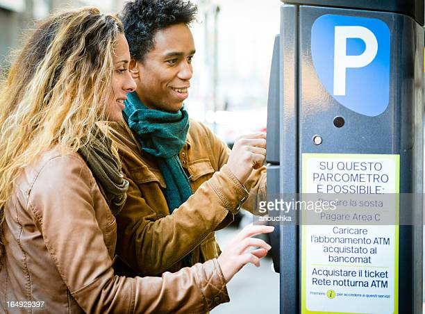 lovely couple using parking ticket machine in the city - parking sign stock photos and pictures