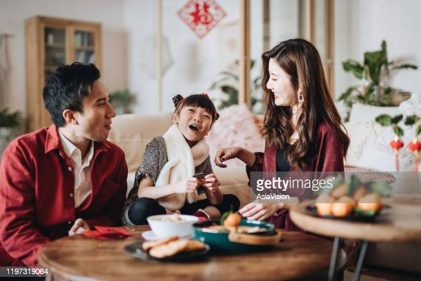 lovely daughter chatting joyfully with father and mother and enjoying family bonding time while celebrating chinese new year at home - snack stock pictures, royalty-free photos & images