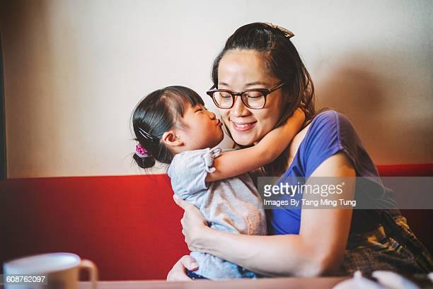 Lovely daughter kissing her mom's cheek