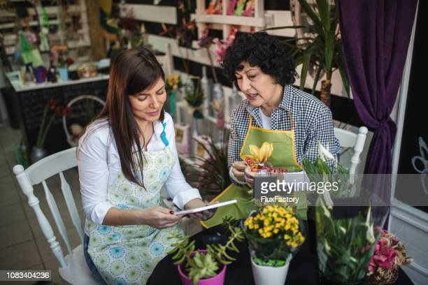 Lovely daughter taking notes about plants from her florist mother