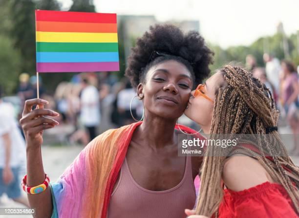 beau couple féminin s'amusant au défilé lgbtqi - gay love photos et images de collection