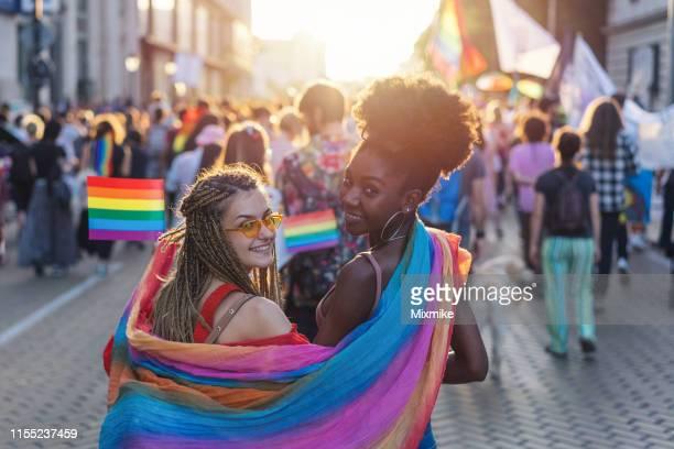 プライドフェスティバルで歩く虹のスカーフと素敵な女性のカップル - ゲイプライドのシンボル ストックフォトと画像