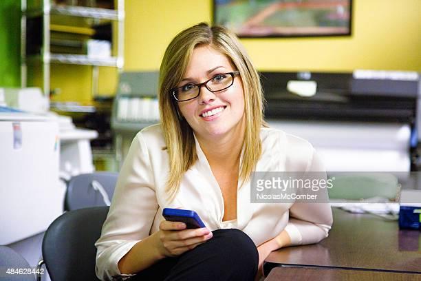 Trabajador de oficina Retrato de mujer hermosa con el teléfono con servicio de impresión remota desde la habitación
