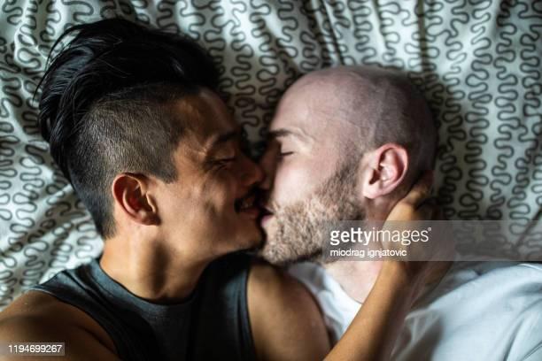 couples gais beaux embrassant dans le bâti - embrasser sur la bouche photos et images de collection
