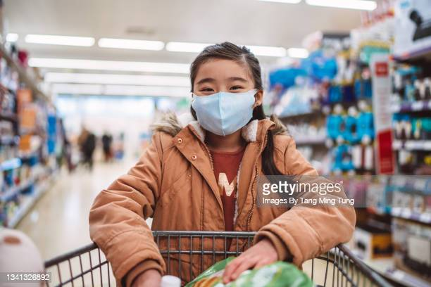 lovely girl in protective face mask shopping in supermarket joyfully - flatten the curve stock pictures, royalty-free photos & images