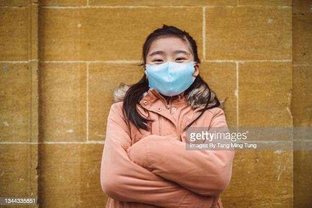 lovely girl in protective face mask smiling joyfully at camera while standing in front of a brick wall with her arms crossed - flatten the curve stock pictures, royalty-free photos & images