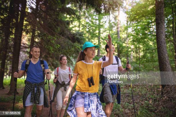 lovely girl leading her friends while hiking - fare da guida foto e immagini stock