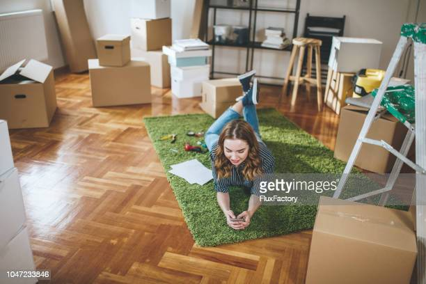 lovely girl lying in her new apartment and texting - one young woman only stock pictures, royalty-free photos & images