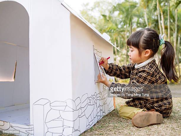 Lovely girl painting on a cardboard playhouse