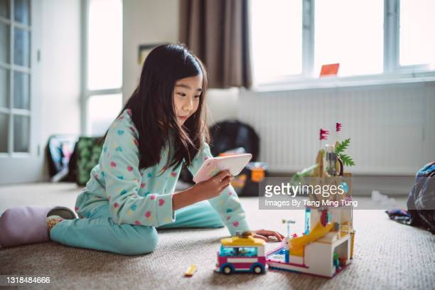 lovely girl showing her block house on video call with smartphone at home - digital native stock pictures, royalty-free photos & images