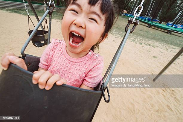 lovely girl swinging joyfully in playground - children only stock pictures, royalty-free photos & images
