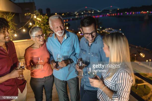Lovely group of diverse age enjoying wine on a rooftop