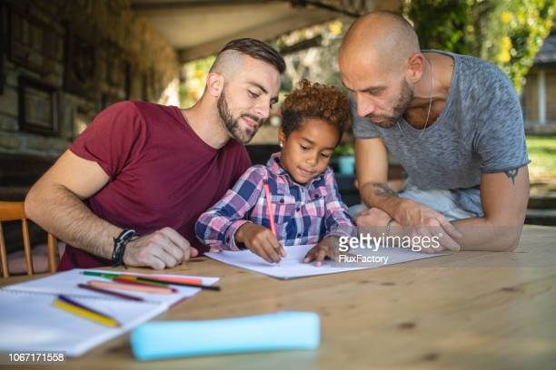 lovely heterosexual couple doing homework with their adopted daughter - gay rights stock pictures, royalty-free photos & images