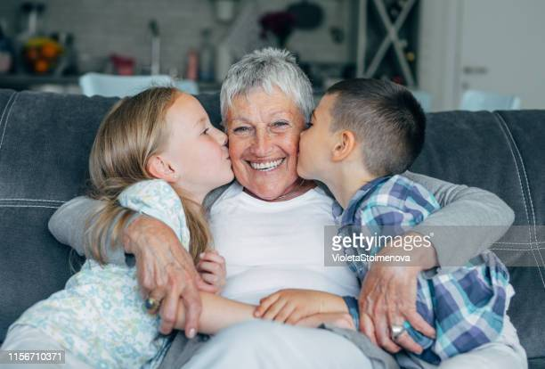 lovely kids kissing their grandmother - grandmother stock pictures, royalty-free photos & images