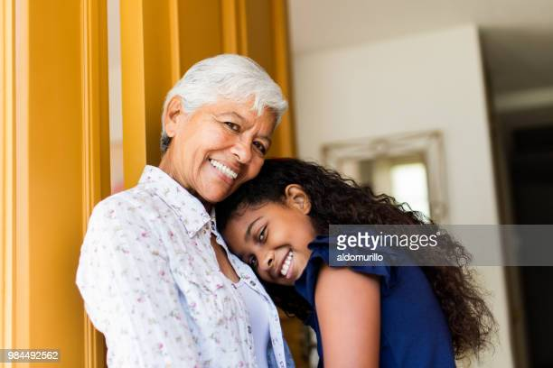Lovely latin grandmother and granddaughter smiling at camera
