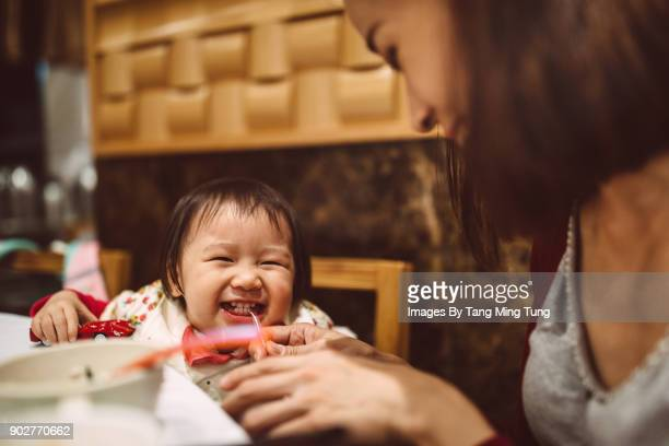 Lovely little baby dining with her pretty young mom in a restaurant joyfully.