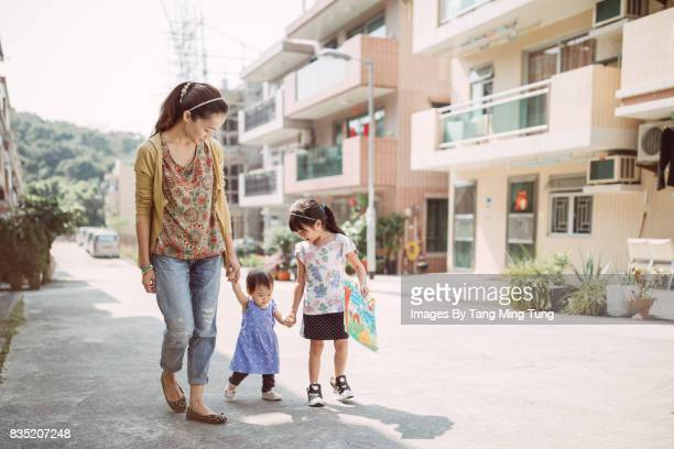 Lovely little baby holding hands with her pretty young mom and her little elder sister while learning to walk joyfully.