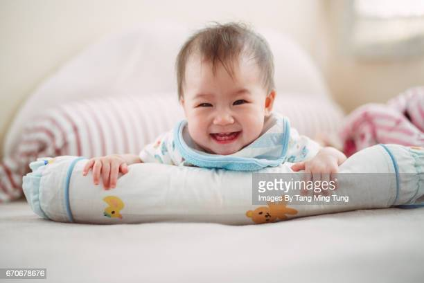lovely little baby hugging a cushion lying on the bed while smiling at the camera joyfully