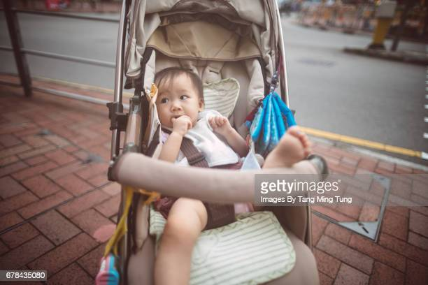 Lovely little baby putting her hand into the mouth sitting and waiting in a stroller.