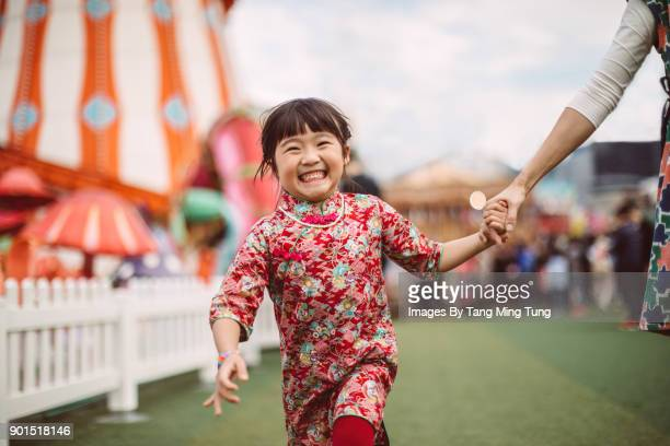 lovely little daughter holding mom's hand running in a carnival joyfully. - 6 7 years photos stock photos and pictures