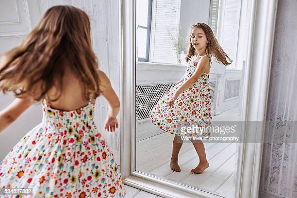 Lovely little girl about 6-10 years in summer dress at the mirror