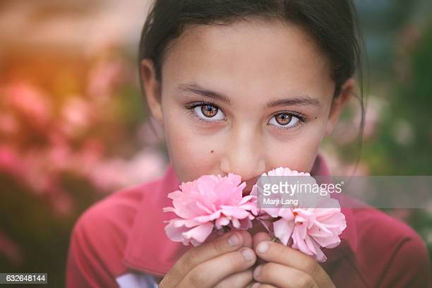 Lovely little girl behind a pair of Damask roses in Konya Central Anatolia region Turkey